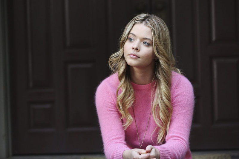 Alison wearing a pink sweater and sitting on her front porch in Pretty Little Liars