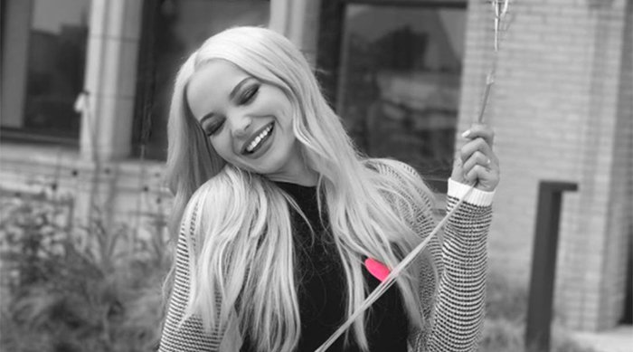 Dove Cameron smiling while holding balloons