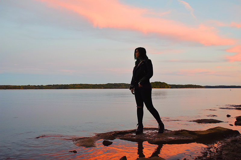 Singer-songwriter LIEZA standing on the edge of a river bed looking at the water