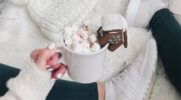 Girl holding a cup of hot cocoa with a gingerbread house on the side