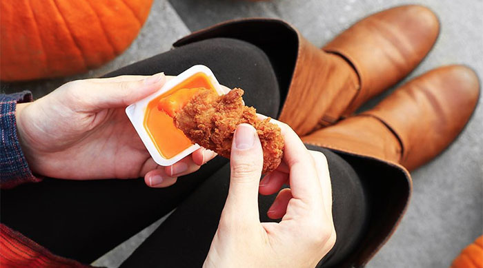 Girl dipping Chick-fil-A chicken strip into buffalo dipping sauce wearing fall clothes