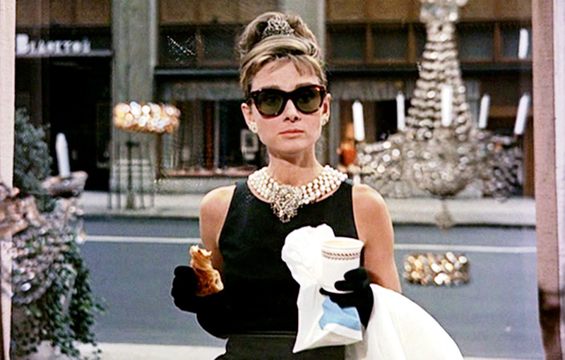Holly Golightl staring into the window of Tiffany's while eating breakfast in Breakfast at Tiffany's