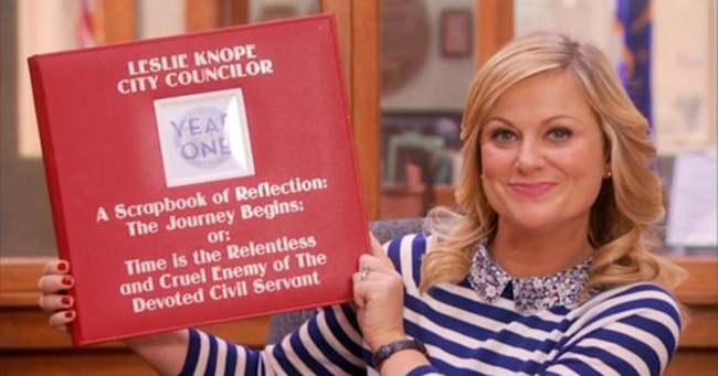 Leslie Knope holding up her council woman binder