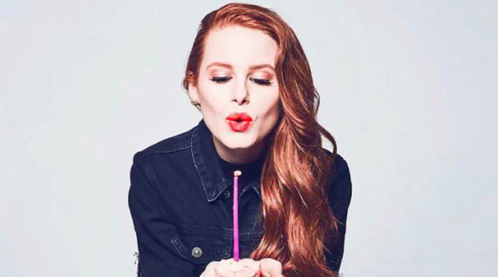 Madelaine Petsch blowing out a candle on a cupcake