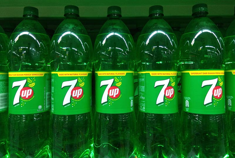 Row of 7 Up bottles on a grocery store shelf