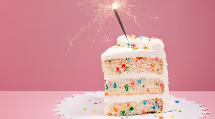 Cute funfetti cake on pink background with sparkler candle