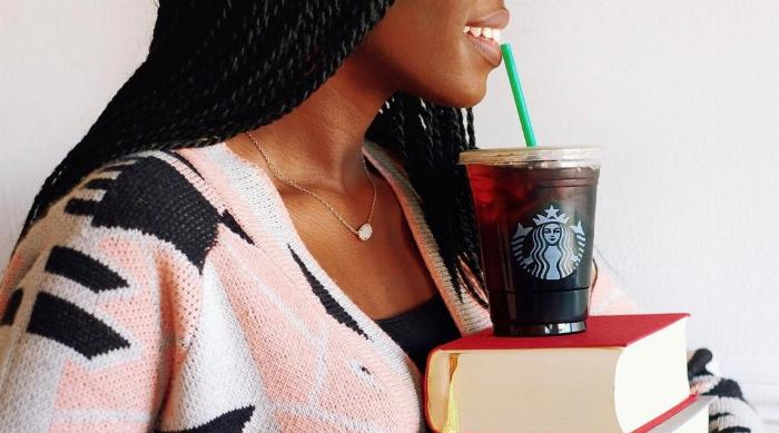 Girl drinking Starbucks coffee off a stack of books