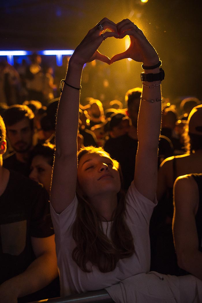 Girl at concert holding up her hands in the shape of a heart
