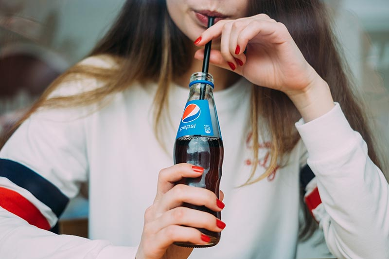 Girl drinking out of a Pepsi bottle with a straw