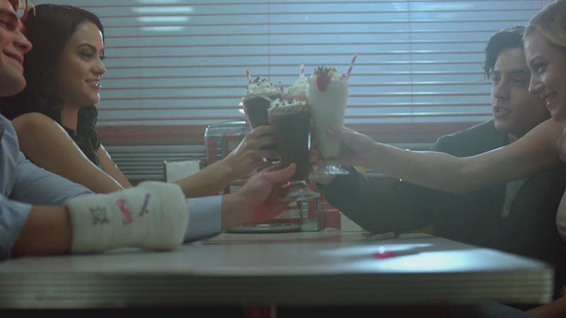 Riverdale characters cheersing with milkshakes at Pop's