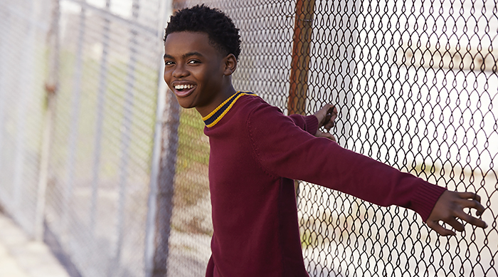 Everything Sucks star Jahi Winston wearing a red sweater and holding onto a fence