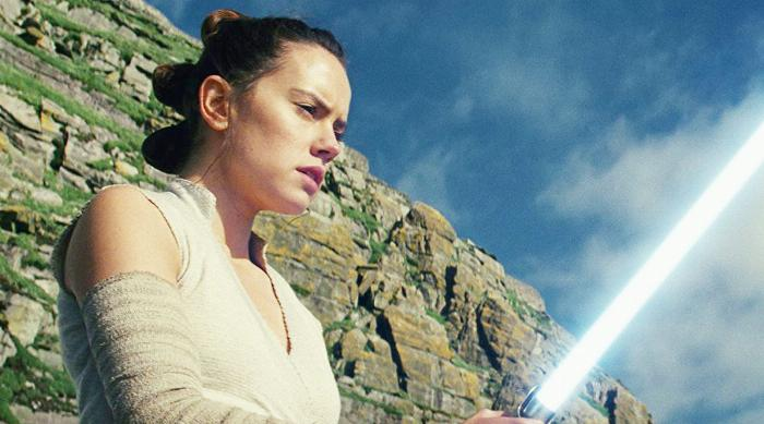 Star Wars: The Last Jedi - Rey looks at a blue lightsaber