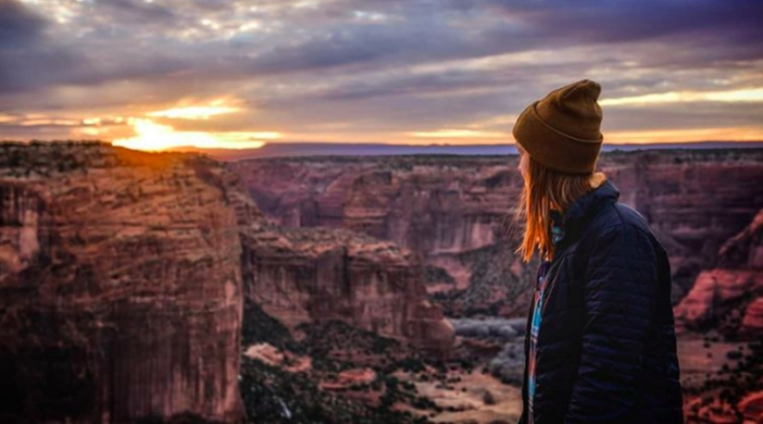 Girl standing on a mountain top looking at the sunset