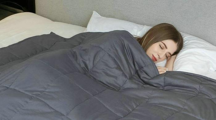 Weighted Idea blankets from Amazon - girl sleeping under dark grey blanket