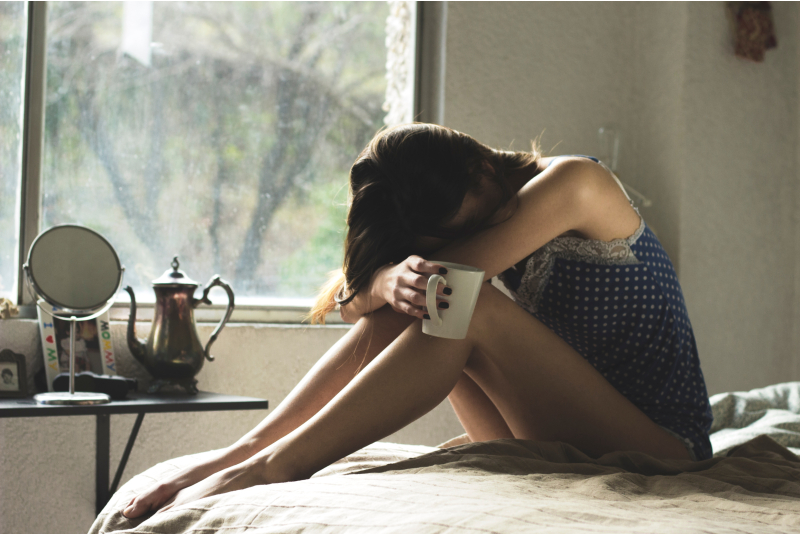 Girl Crying while holding a coffee cup