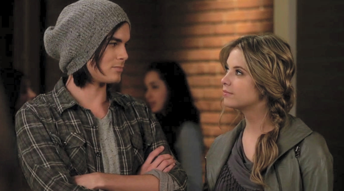 Hanna and Caleb smirking at each other on an episode of Pretty Little Liars