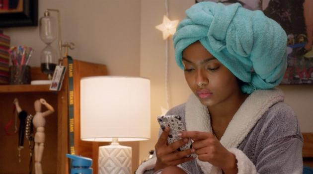 Zoey with a towel turban on her head sitting on her bed and looking at her phone in Grown-ish