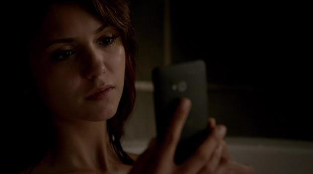 Elena Gilbert staring sadly at her phone on The Vampire Diaries