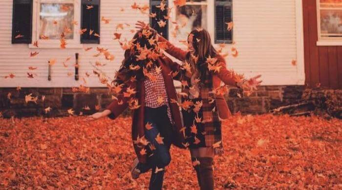 girls playing fall leaves