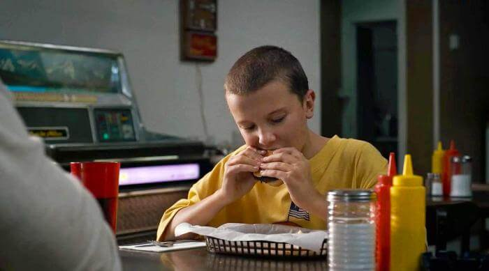 Stranger Things: Eleven hungrily eating a hamburger