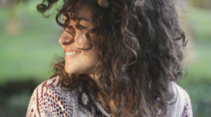 girl with curly hair smiling