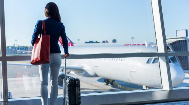 shutterstock-woman-with-carry-on-bag-looking-at-plane-articleH-100218