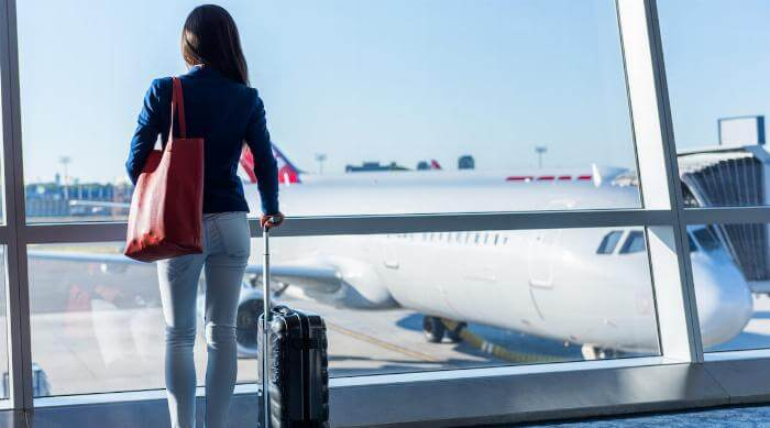 Shutterstock: Woman with her carry-on luggage looking out airport window at airplane