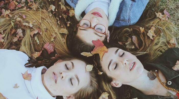 Unsplash: Three girls with heads touching laying in fall leaves