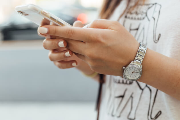 Woman with painted nails and a watch holding a phone