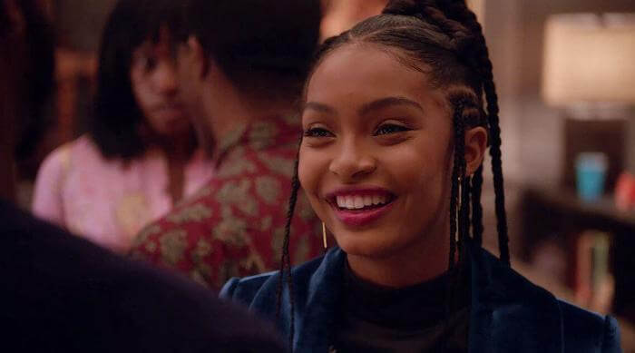 Zoey smiling while talking to someone in Grown-ish