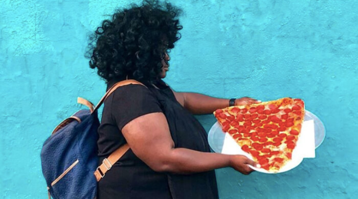 Girl holding a large slice of pepperoni pizza in front of a blue wall