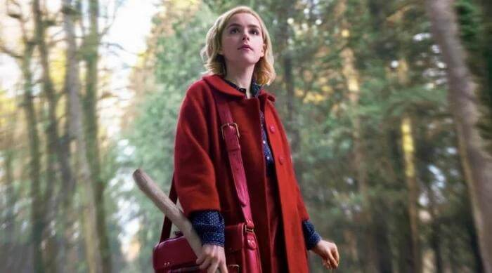 Sabrina Spellman in the middle of the woods summoning the weird sisters in Netflix's Chilling Adventures of Sabrina