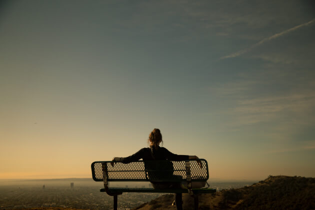 Unsplash: woman sitting on a bench at a scenic overlook
