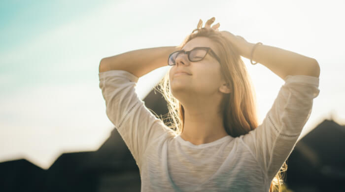 Unsplash: woman smiling with her hands on her head