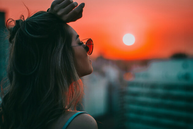 Unsplash: woman standing facing the sunset with her hand on her forehead