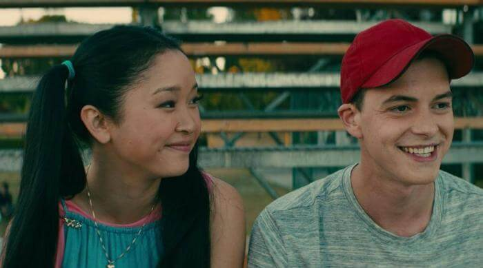 Lara Jean smiling at Josh while sitting on the bleachers in a scene from To All the Boys I've Loved Before
