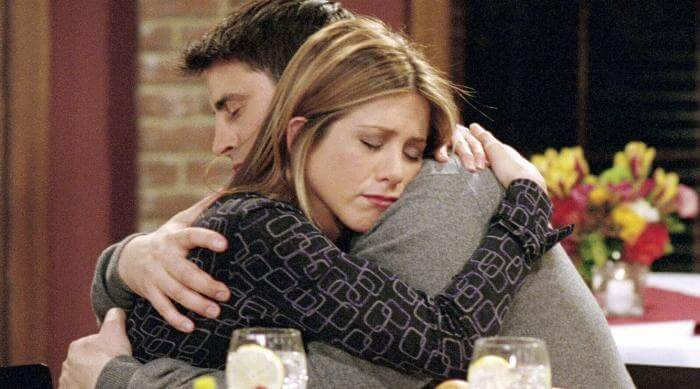 Ross and Rachel hugging each other over dinner during an episode of Friends
