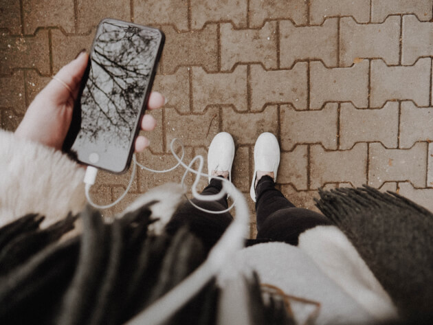 Unsplash: Woman holding a phone with headphones
