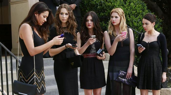 The girls of Pretty Little Liars all looking at their phones after receiving a message from A