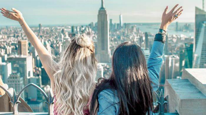 Unsplash: Court Prather - Two girls celebrating a scenic view of buildings best friends sisters