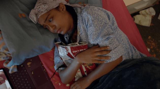 Zoey upset in bed cradling a bag of chips in Grown-ish