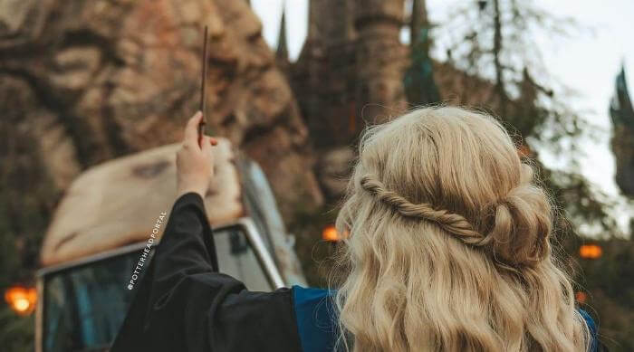 Instagram: Potterheadportal photo of woman with wand in front of Hogwarts Castle at Wizarding World of Harry Potter