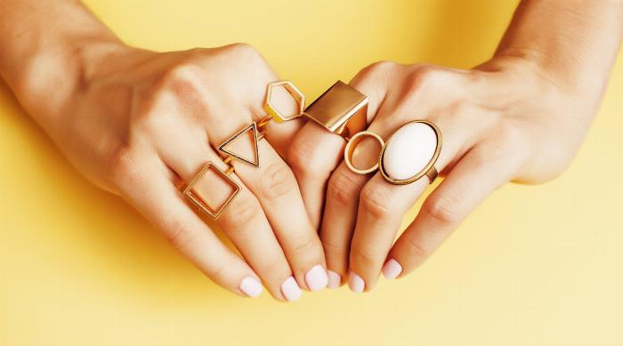 Shutterstock: Hands with lots of rings on yellow background