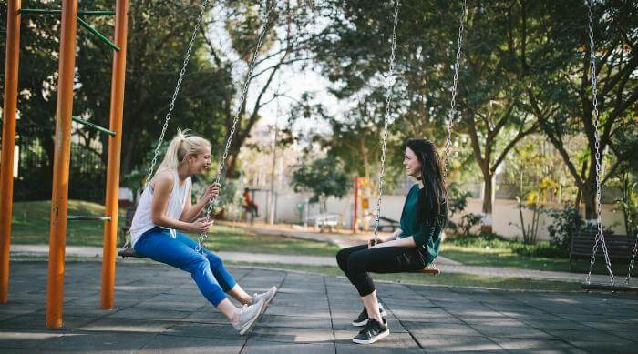 two girls sitting on swings