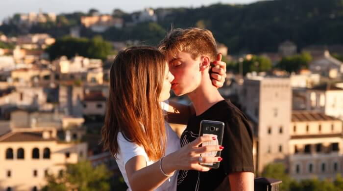 unsplash - couple kissing while taking a picture
