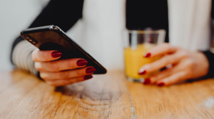 girl holding phone with red nails