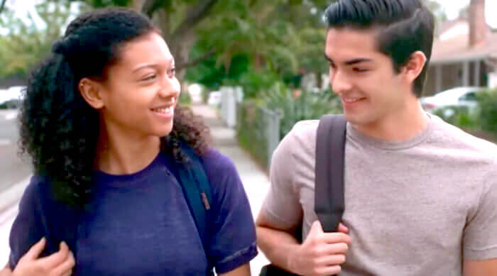 Monse and Cesar smiling at each other while walking to school in a scene from On My Block