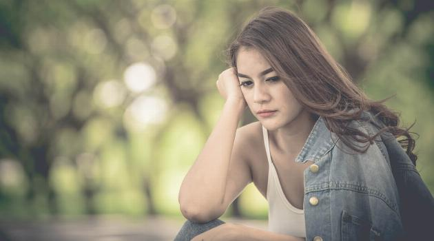 Shutterstock: Woman in park pouting, thinking and looking sad