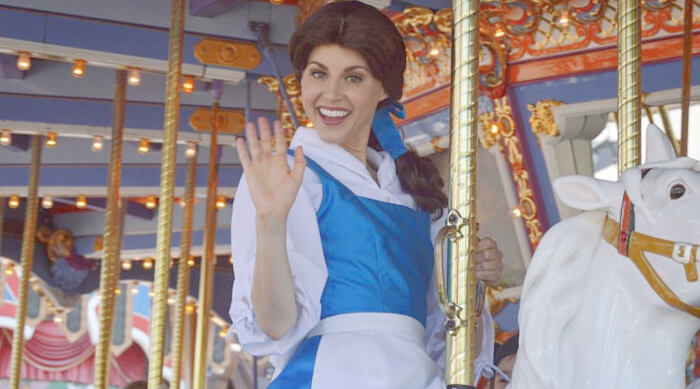 Character actor dressed up as Belle in her blue and white getup waving at the camera while riding the King Arthur Carrousel at Disneyland