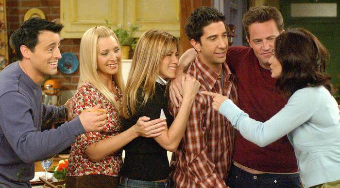 NBC Friends: Main characters in a line hugging and laughing